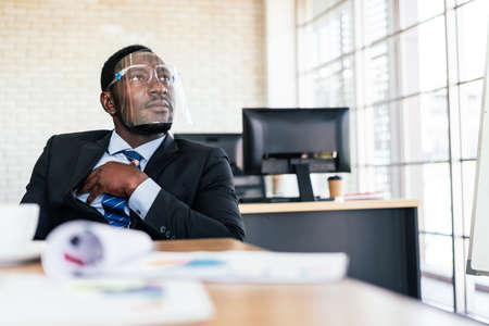 African businessman wearing a face shield, listens and shares his opinion at a business group meeting, Discussion a new business plan in the office. Diversity of businesspeople. Image with copy space.