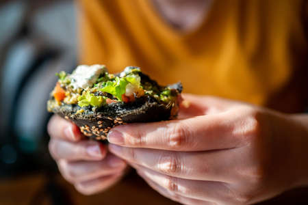Hands holding Broccoli quinoa charcoal burger topped with guacamole, mango salsa and fresh salad in cut half is bitten. Creative vegan meal for vegetarians. 免版税图像