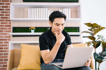 Asian male in casual feels stress and concerned with laptop while working and sitting on the sofa. Businessman working with problems on a laptop at home. Solving the problem process in business. Reklamní fotografie