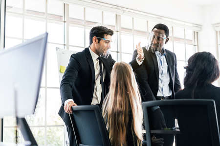 African businessman wearing a face shield, looking at his colleagues at a business group meeting, Discussion a new business plan in the office. Diversity of businesspeople. Image with copy space.