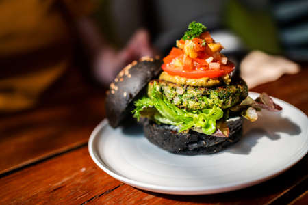 Broccoli quinoa charcoal burger topped with guacamole, mango salsa and fresh salad served on a white plate. Creative vegan meal for vegetarians. 免版税图像