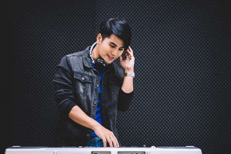 Asian male playing an electric keyboard while wearing headphones in the recording studio. Recording songs by using a studio microphone with copy space.
