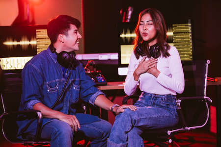 A pretty Asian female tries to sing with her producer in the studio in a rehearsal session. Performance and show in the music business. Image with copy space. Small and home recording studio. Stock Photo