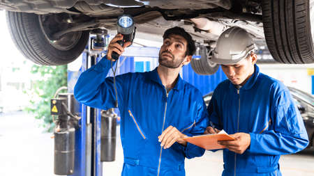 Mechanic and his assistant examining the car bottom with flash light. Auto car repair service center. Professional service.