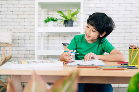 The child's drawing with colored pencils on white paper with smiling on a wooden table. Children's creativity expressed through art in kindergarten and elementary school. back to school. Reklamní fotografie