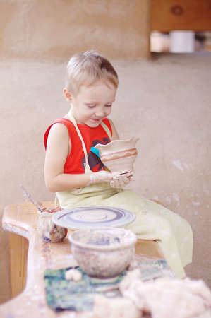 the kid is making a pitcher on the potter's wheel