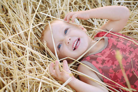 Portrait of little boy in a summer hat sitting on a haystack in a field of wheat