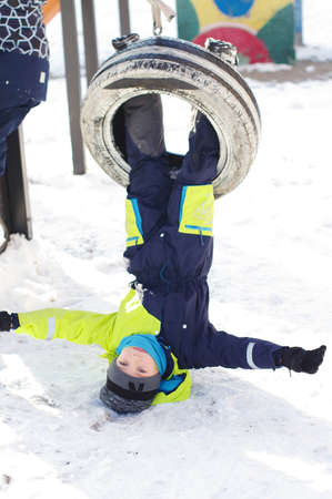 Cute  little boy ride on a swing  in winter.  happy children having fun, playing at winter walk outdoors