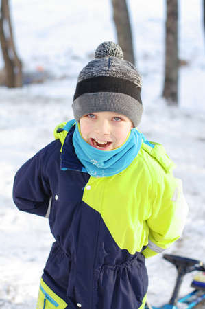 Children play outdoors in snow. Happy boy playing on a winter walk in nature Stok Fotoğraf