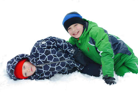 Children play outdoors in snow. Happy boys playing in winter Banco de Imagens - 119476762