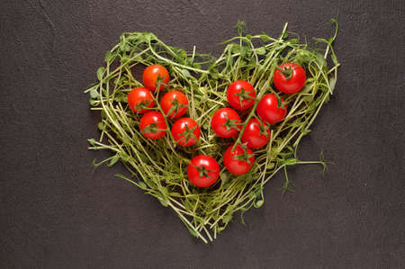 heart made of young pea shoots and cherry tomatoes on black background; Heart symbol. Vegetables diet concept Stock fotó