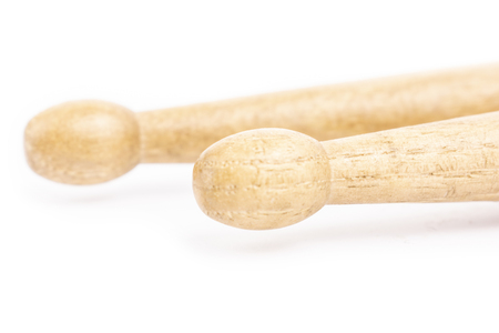 Two wooden drumsticks lying, isolated on a white background