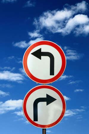 two opposite road signs against blue sky and clouds photo