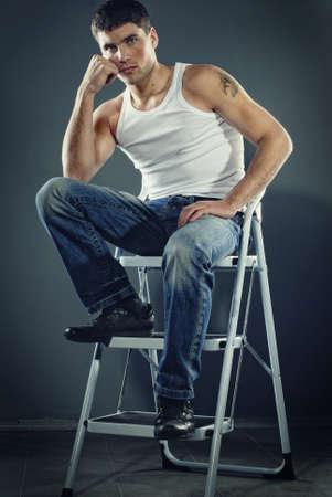 hombre sucio: atractivo hombre en pantalones vaqueros sentados en las escaleras Foto de archivo