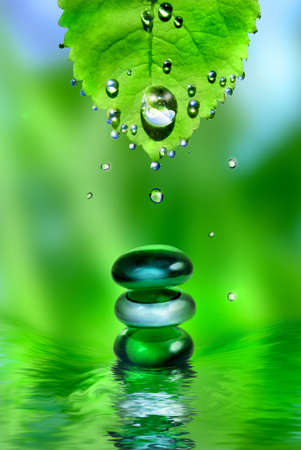 balancing spa shiny stones with leaf and water drops on green background Stock Photo
