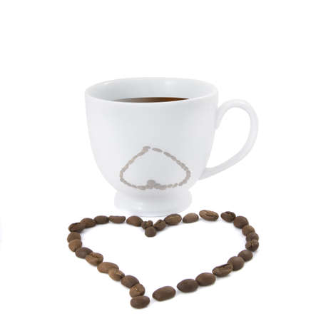 Coffee cup with heart from coffee beans isolated on white photo