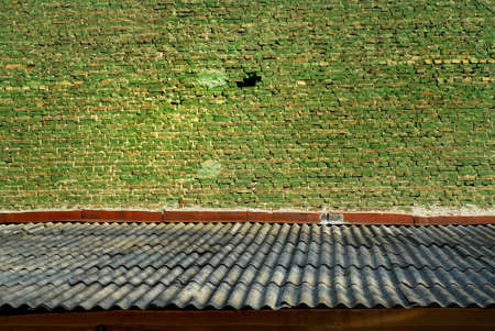 shiver: Old green bricks wall and shiver roof Stock Photo
