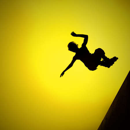 silhouette of roller boy jumping in air photo