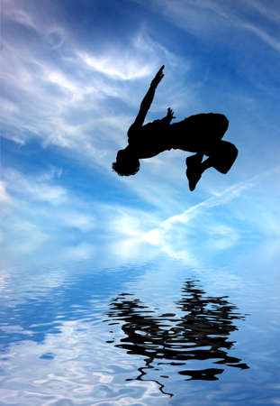 silhouette of jumping man against blue sky and clouds Stock Photo