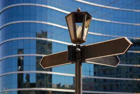 Blank signpost with ancient lamp against business building Stock Photo