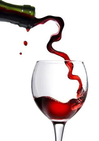 wine pouring: Versare il vino rosso nel calice in vetro isolato su bianco