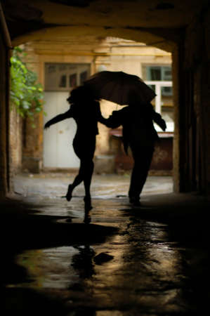 silhouette of couple with umbrella running from rain Stock Photo