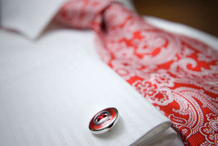 tailored: close-up photo of stud on white shirt with red tie