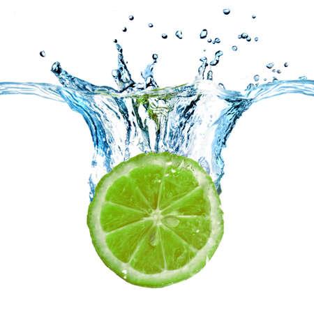 Fresh lemon dropped into water with splash isolated on white photo