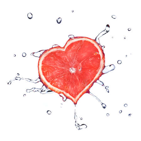 heart from grapefruit dropped into water with splash isolated on white photo