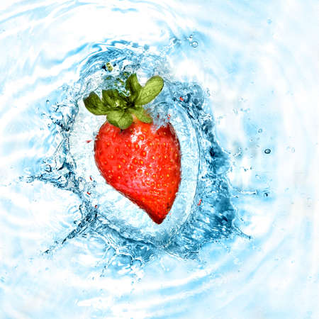 heart from strawberry dropped into water with splash isolated on white photo