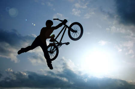 bmx bike: silhouette of boy with bicycle jumping in air Stock Photo