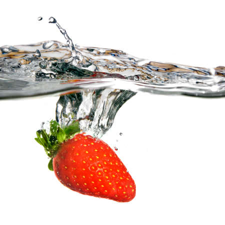 Fresh strawberry dropped into water with splash isolated on white photo