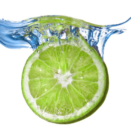 Fresh lime dropped into water isolated on white photo