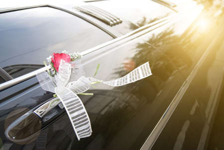 Door of black wedding car with flower and  ribbon photo