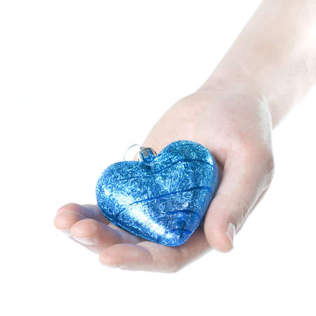 arm holding blue christmas ball in shape of heart isolated on white photo