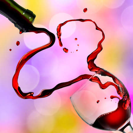 Heart from pouring red wine in goblet on color background photo