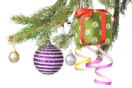 Christmas balls, gift and decoration on fir tree branch isolated on white photo