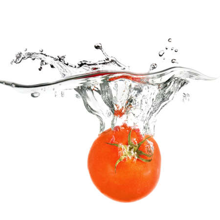 red tomato dropped into water isolated on white photo