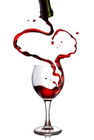 wine pouring: Vino rosso, versando in calice da bottiglia a forma di cuore Archivio Fotografico