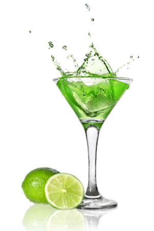 Green alchohol cocktail with splash and green lime isolated on white