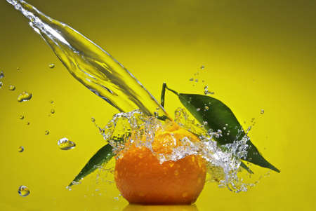 Tangerine with green leaves and water splash on green background photo