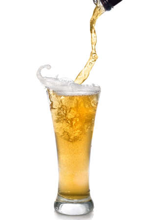 Beer pouring from bottle into glass isolated on white photo