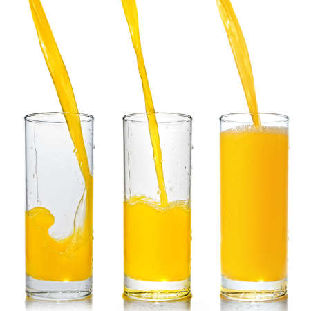 orange juice poring into glass isolated on white photo