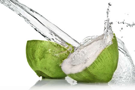 Green coconut with water splash isolated on white Фото со стока