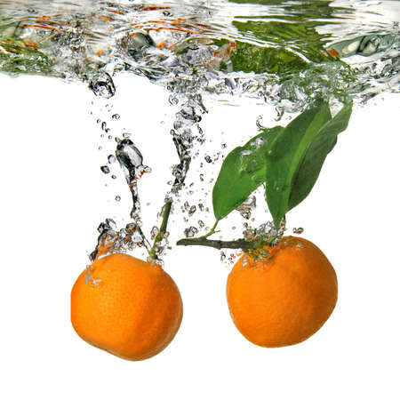 tangerines dropped into water with bubbles on white photo