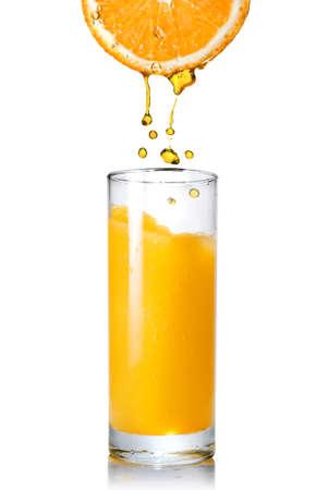 jus orange glazen: Gieten van sinaasappel sap van oranje in op wit wordt geïsoleerd glas  Stockfoto