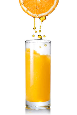 verre jus orange: Pouring orange juice from orange into the glass isolated on white Banque d'images