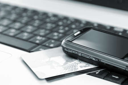technology transaction: Credit cards and mobile phone on the notebook