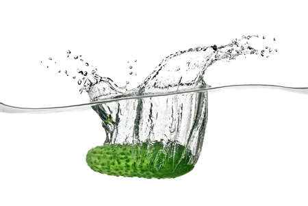 dropped: green cucumber dropped into water isolated on white