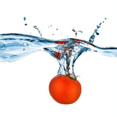 dropped: red tomato dropped into water isolated on white Stock Photo